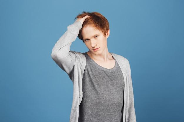 Czy jestem wystarczająco piękna i wspaniała, dziewczyno portret pewnej siebie młodej imbirowej nastolatki w swobodnym stroju dotykającej włosów dłonią, z zalotnym i narcystycznym wyrazem twarzy.