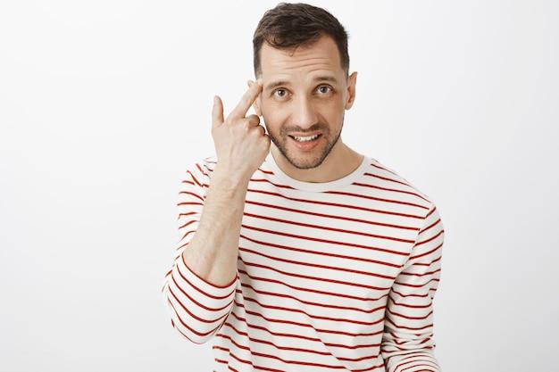 Czy jesteś szalony. portret wkurzony przystojny chłopak w pasiastym swetrze, toczący palec wskazujący