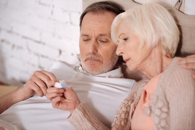 Czy jesteśmy chorzy? bliska portret starszej pary leżącej na łóżku i patrząc na termometr w celu sprawdzenia temperatury.