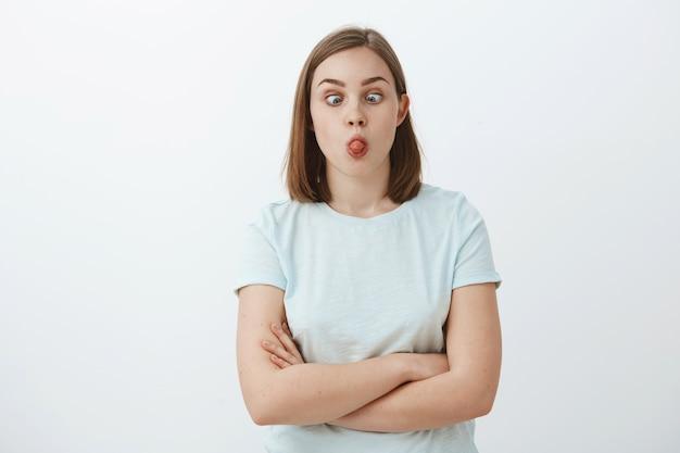 Czy możesz dotknąć nosa językiem. portret śmiesznej figlarnej i niedojrzałej uroczej kobiety z krótkimi brązowymi włosami mrużącymi oczy, robiącymi miny i wygłupiając się, bawiąc się na szarej ścianie