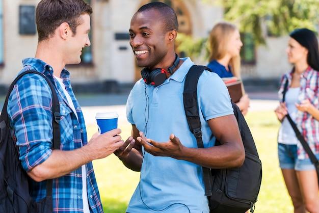 Czy możesz w to uwierzyć? dwóch młodych mężczyzn rozmawiających ze sobą i uśmiechających się, podczas gdy dwie kobiety stoją w tle