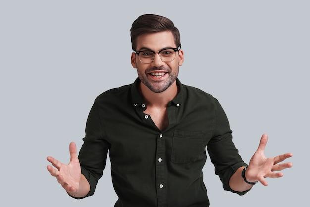 Czy możesz w to uwierzyć? przystojny młody mężczyzna w okularach, gestykulujący i patrzący na kamerę z uśmiechem, stojąc na szarym tle