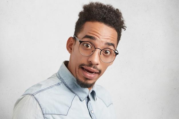 Czy naprawdę tak jest? zaskoczony kujon mężczyzn rasy mieszanej wygląda w oszołomieniu, nosi okrągłe okulary,