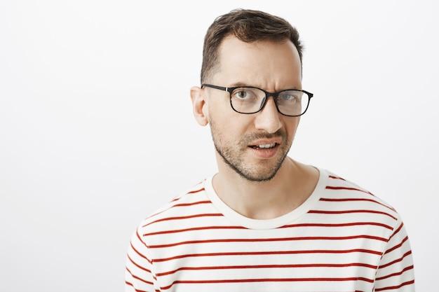 Czy ty żartujesz. niezadowolony wahający się atrakcyjny facet w czarnych modnych okularach, unoszący jedną brew