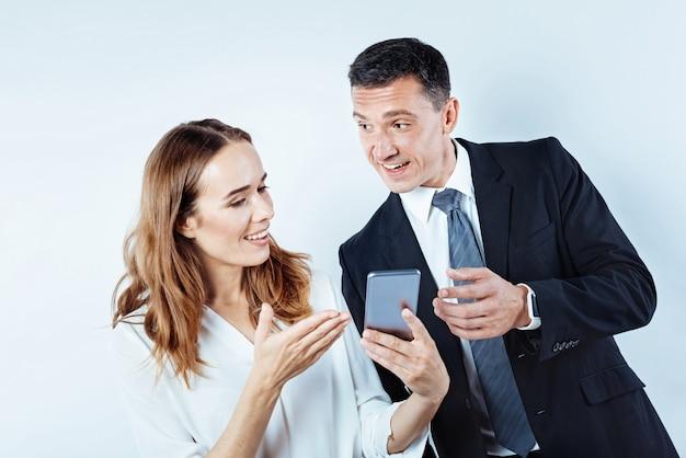 Czy wiedziałeś. ujęcie w górę przyjaznych biznesmenów, którzy robią sobie przerwę i plotkują o czymś podczas korzystania ze smartfona.