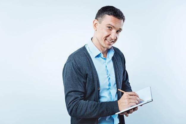 Czy wiedziałeś. zaciekawiony mężczyzna patrzy w kamerę z lekkim uśmiechem na twarzy, trzymając ołówek i zapisując pewne informacje w swoim notatniku.