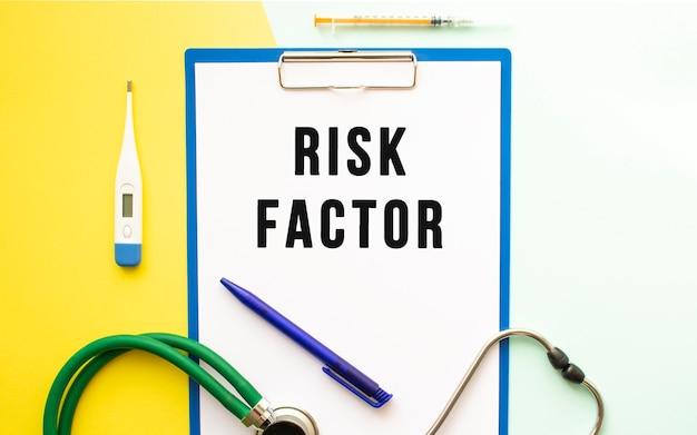 Czynniki ryzyka tekst na papierze firmowym w folderze medycznym na pięknym tle. stetoskop, termometr i długopis.