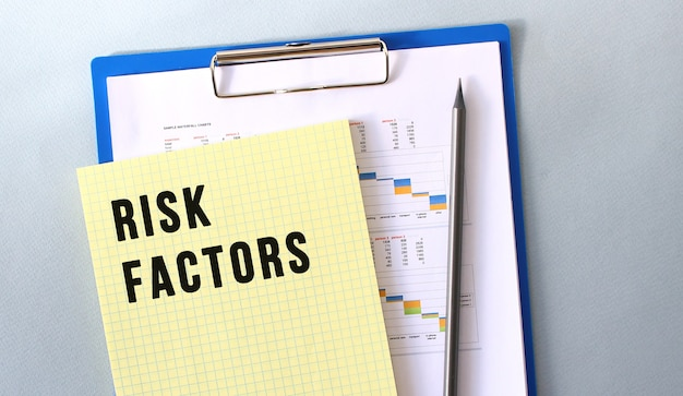 Czynniki ryzyka tekst zapisany na notatniku ołówkiem. notatnik na teczce z diagramami. koncepcja finansowa.