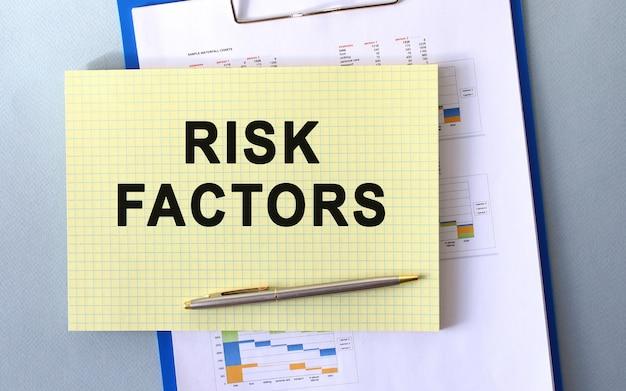 Czynniki ryzyka tekst zapisany na notatniku ołówkiem. notatnik na teczce z diagramami.