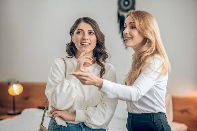 Czynsz za mieszkanie. młoda kobieta rozmawia z agentem nieruchomości o wynajmie mieszkania i wygląda na zaangażowaną