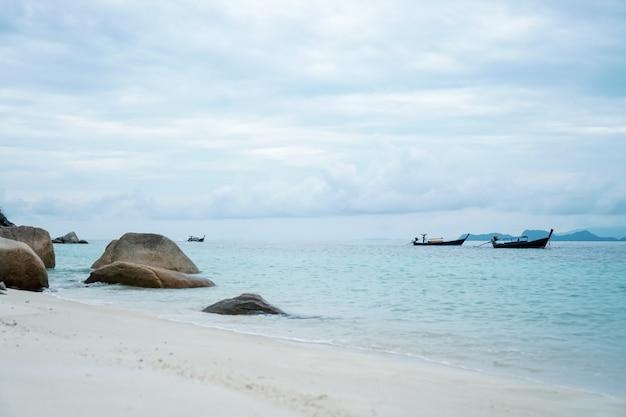 Czyści plażę i białego piasek w lecie z słońca bławym niebem i bokeh tłem.