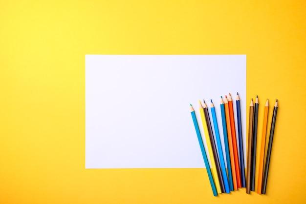 Czysta biała kartka i kolorowe kredki do rysowania na żółtym tle