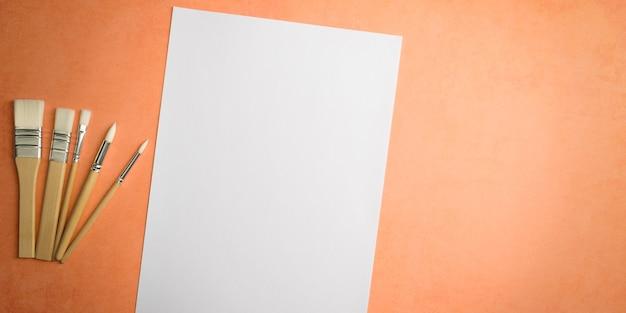 Czysta biała kartka i pędzle na teksturowanym tle z miejscem na skopiowanie układu