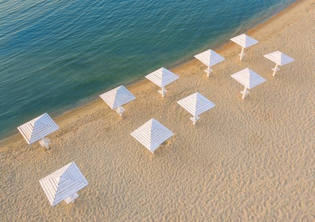 Czysta czysta plaża z drewnianymi parasolami, widok z lotu ptaka.