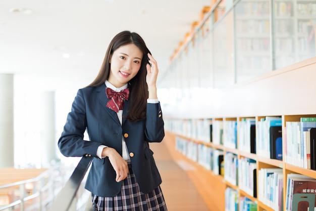 Czysta i urocza piękna studentka w bibliotece.