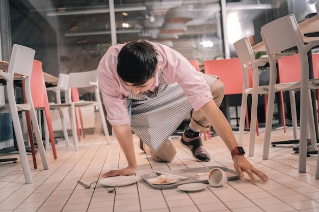 Czysta podłoga. młody ciemnowłosy kelner sprzątający podłogę po upuszczeniu tacy z jedzeniem i kawą