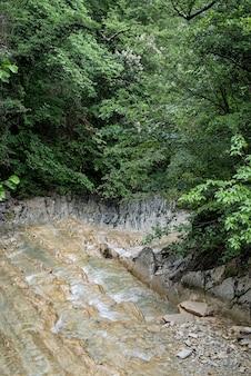 Czysta rzeka ze skałami prowadzi w kierunku gór oświetlonych zachodem słońca