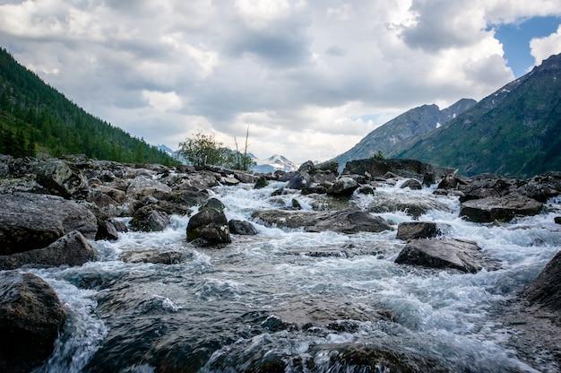 Czysta rzeka ze skałami prowadzi w stronę gór. rzeka wpada do jeziora