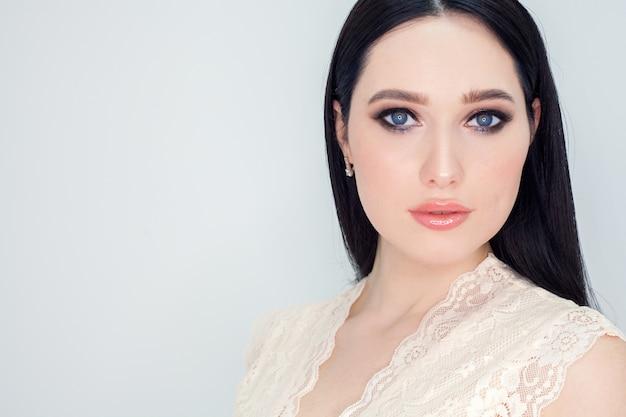 Czysta twarz z młodą skórą, portret kobiety na białej ścianie. zdjęcie koncepcyjne reklamujące produkty i kremy do mycia twarzy z efektem liftingującym.