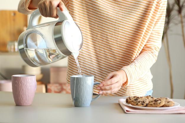 Czysta woda gotuje się w czajniku elektrycznym na stole w kuchni