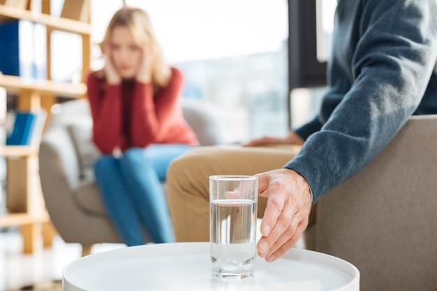 Czysta woda. selektywne skupienie się na szklance wody stojącej na stole podczas przebywania w gabinecie psychologa przez przystojnego przystojnego mężczyznę