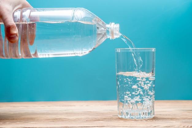 Czysta, zdrowa, chłodna woda wlewa się do szklanki z plastikowej butelki