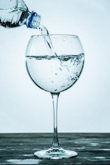 Czysta, zdrowa gazowana woda wlewa się z butelki do przezroczystej szklanki