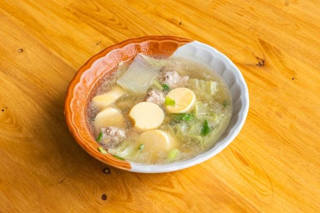 Czysta zupa z tofu i mieloną wieprzowiną na drewnianym stole, zbliżenie i widok z góry.