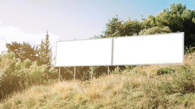 Czyste białe billboardy na zielonym zboczu