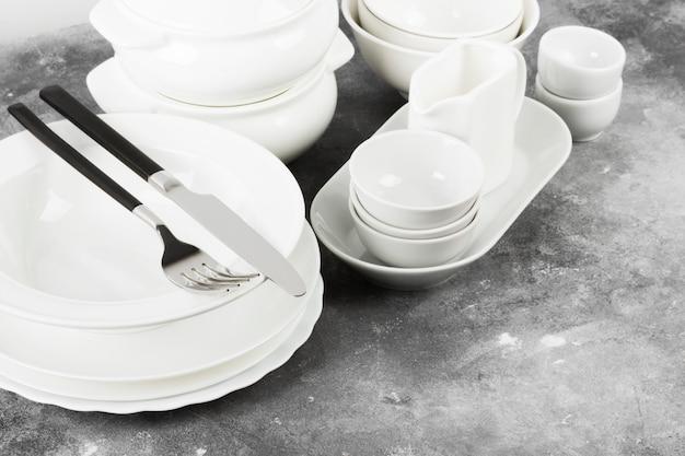 Czyste białe naczynia na szarym tle. skopiuj miejsce
