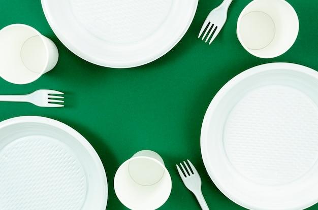 Czyste białe naczynia na zielonym tle