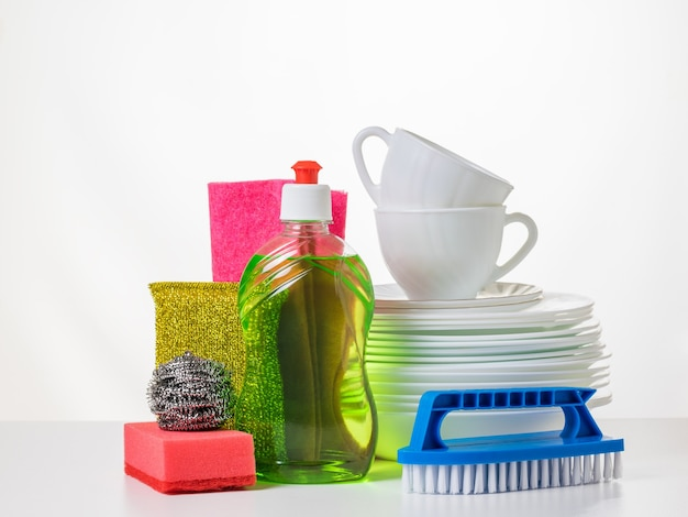 Czyste białe porcelanowe naczynia i zestaw do mycia na białym stole. pojęcie czyszczenia i utrzymania czystości.