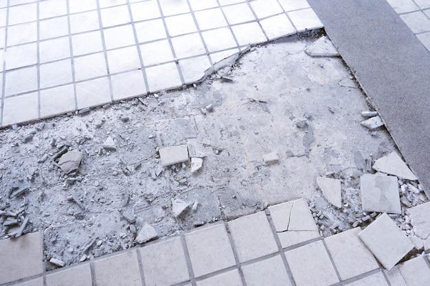 Czyste białe złamane tło tekstury ściany z płytek. podłoga z płytek wybuchła i pękła, ponieważ była używana przez długi czas, naprawa płytek w domu