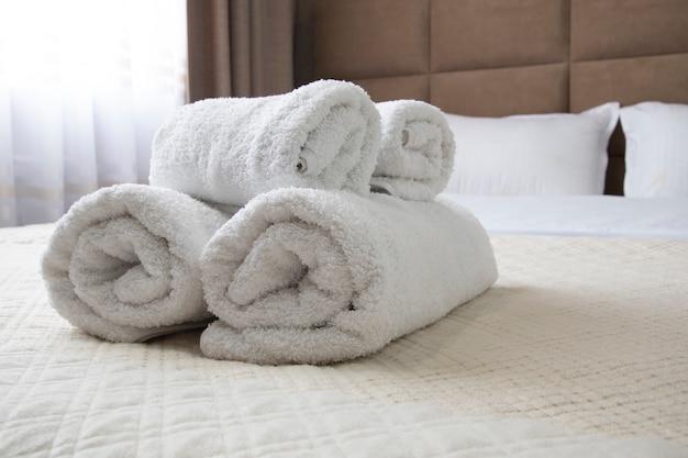Czyste białe zwinięte ręczniki leżą na łóżku. zbliżenie