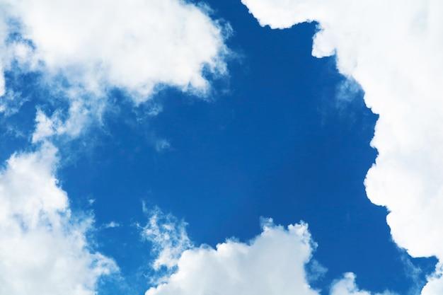 Czyste błękitne niebo kupa białą chmurę i światło słoneczne i kopiuje przestrzeń na środkowym niebie