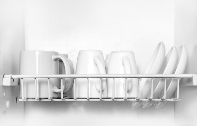 Czyste naczynia suszące się na metalowym stojaku na naczynia na półce