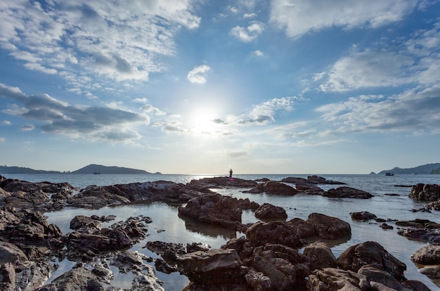 Czyste niebo białe chmury w słoneczny dzień i skały na pierwszym planie, sylwetka wędkarza na kamieniach nad morzem pod błękitnym letnim niebem.