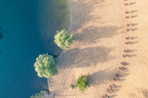 Czyste piaszczyste leżaki i turkusowa woda. widok z góry.