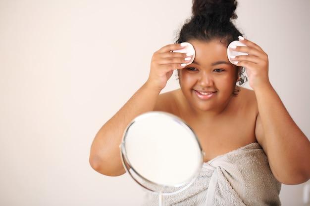 Czyste piękno. piękna młoda kobieta african american, dotykając jej twarzy.
