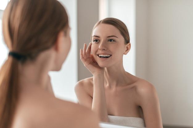 Czyste piękno. przez ramię widok atrakcyjnej kobiety dotykającej jej twarzy i uśmiechającej się podczas patrzenia w lustro
