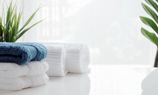 Czyste ręczniki i rośliny doniczkowe na białym stole.