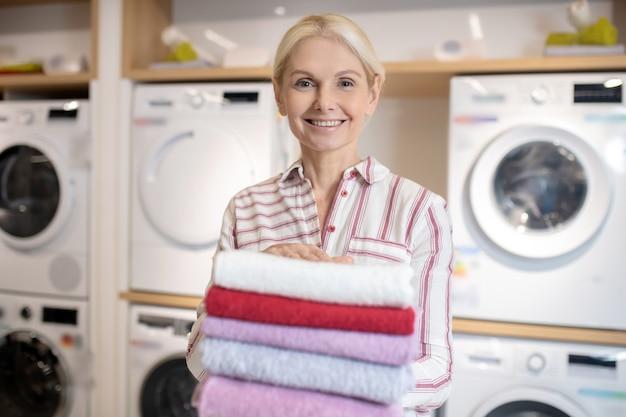 Czyste ręczniki. uśmiechnięta blondynka trzyma stos ręczników
