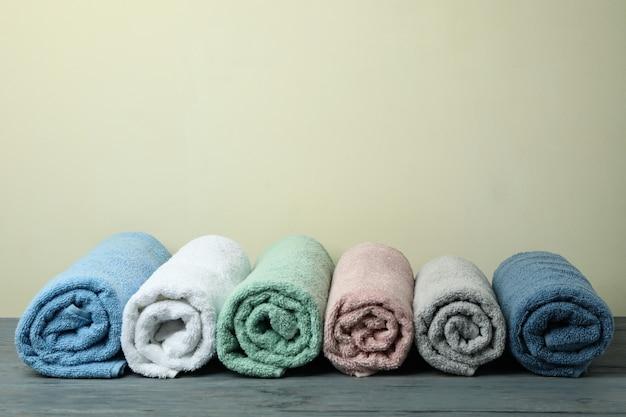 Czyste ręczniki walcowane na beżowym tle, miejsce na tekst