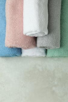 Czyste ręczniki walcowane na tle z teksturą, miejsce na tekst