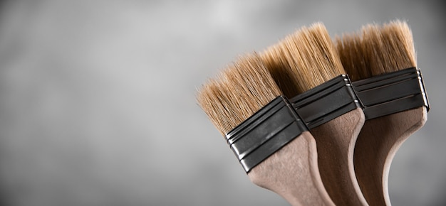 Czyste, świeże, nowe pędzle do malowania na szarym, rozmytym tle betonu. zamknij się z kopii puste miejsce na tekst. baner reklamowy.