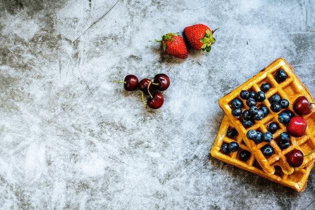 Czyste tło z czerwonymi owocami i gofrem