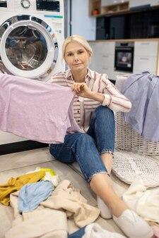 Czyste ubrania. blond gospodyni domowa w pasiastej koszuli siedzi w pobliżu pralki i trzyma ubrania