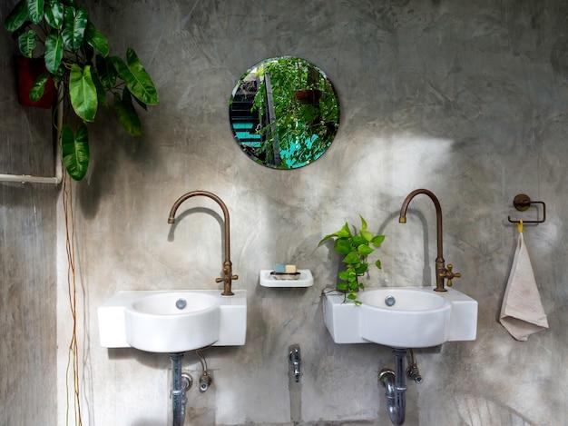 Czyste wnętrze łazienki w stylu loftu z dwiema białymi nowoczesnymi umywalkami, mosiężnymi kranami, zielonymi liśćmi w doniczce i okrągłym lustrem na betonowej ścianie