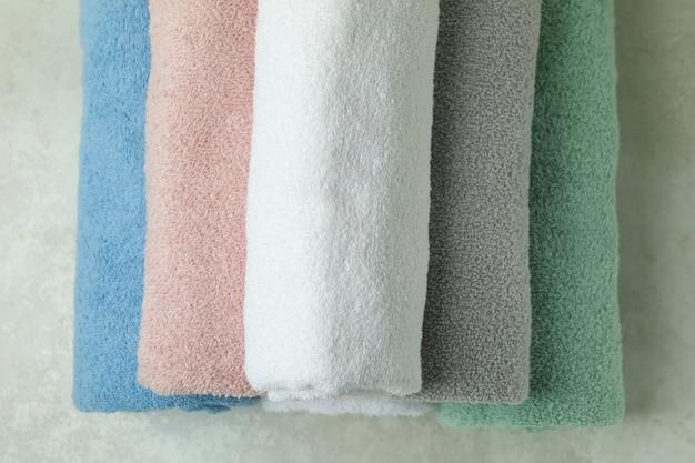 Czyste zrolowane ręczniki na teksturowanym widoku z góry