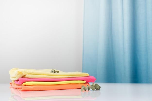 Czysto pachnące ubrania do prania o jasnych kolorach są ułożone w stos.
